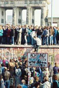 People atop the Berlin Wall near the Brandenburg Gate on November 9, 1989.